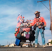 Man with all his belongings in a shopping trolley covered in american flags, USA