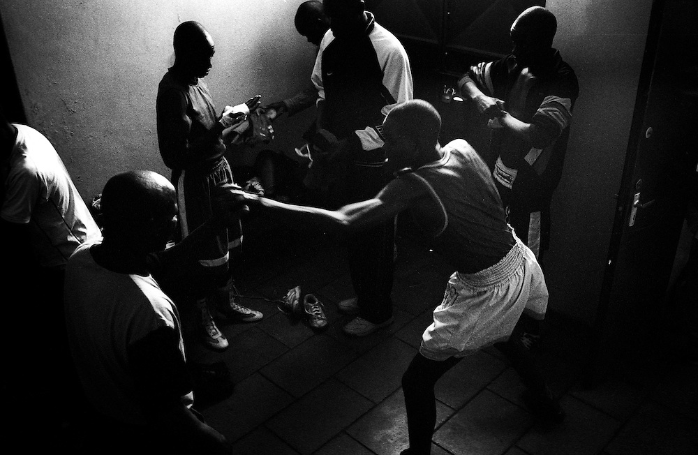 NAIROBI, KENYA - MARCH 18, 2010: Young athletes prepare for their turn to compete in a bout featuring the Kibera Olympic Boxing Club, Kenya Prisons and the Kenya Police and Armed Forces (AFABA). Each year, Kibera Olympic boxers aspire individually to make the national team, and the opportunity to compete in the annual Kenya Open boxing tournament. In previous years, boxers from Kibera slum have gone on to win tournaments on both the national and international stage.<br /> <br /> Within Kenya's progressive youth culture is the Kibera Olympic Boxing Club, a group of low-income adolescents from the slum whose leader uses boxing as a way to engage with idle youth. The group's ethnic diversity is remarkable given Kenya's 2008 post-election violence in which people from several tribes were forced violently out of slums. Together, these boxers represent a nascent trend of cross-tribe brotherhood in a healing nation.
