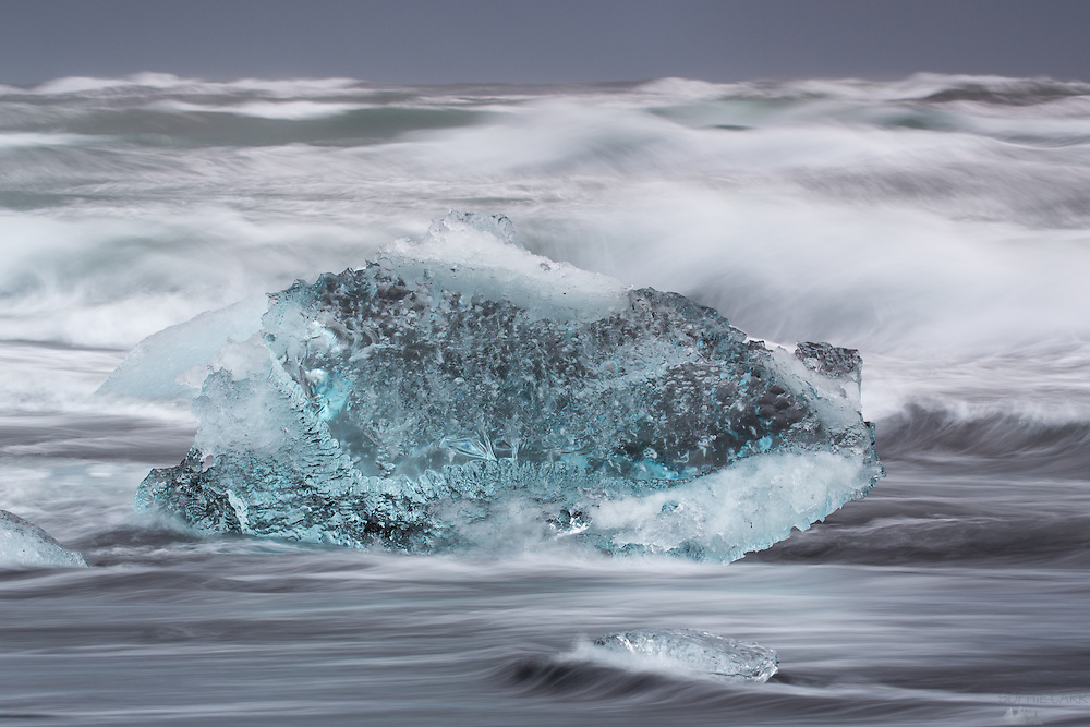 Waves crash over icebergs on Jökulsárlón Beach, leaving picturesque water trails