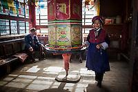 Senior Tibetean woman walks around the small traditional stupa repeating prayers.