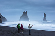 Tourist at Reynisdrangar basalt sea stacks (troll rocks) and black volcanic sand beach Reynisfjara near Vík i Myrdal, South Iceland