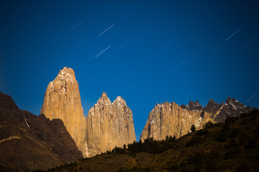 Gigantic granite monoliths shaped by the forces of glacial ice known as the three Towers of Paine at night with star trails in Torres del Paine National Park, Chile.