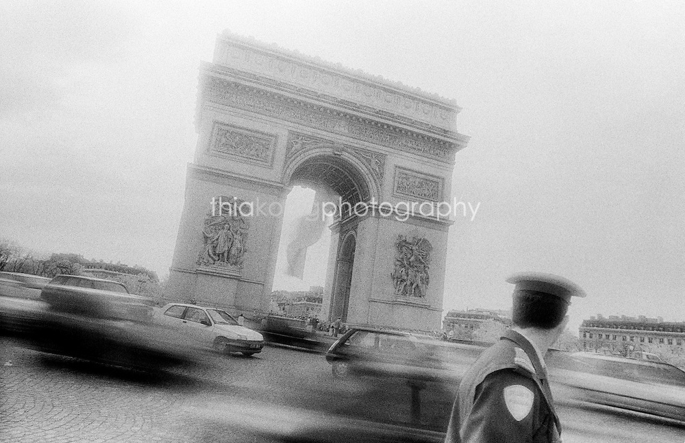 A gritty, off angle view looking over a policeman's shoulder to the traffic swirling around the Arc de Triomphe, Paris