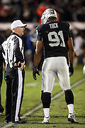 Oakland Raiders defensive end Justin Tuck (91) talks to referee John Parry (132) during the NFL week 12 regular season football game against the Kansas City Chiefs on Thursday, Nov. 20, 2014 in Oakland, Calif. The Raiders won their first game of the season 24-20. ©Paul Anthony Spinelli
