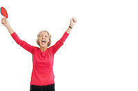 Happy senior female table tennis player with arms raised celebrating victory
