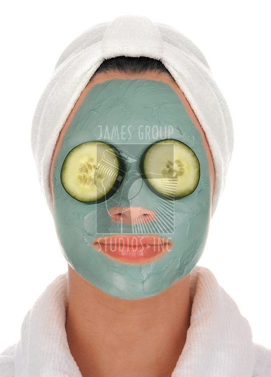 front view of a beautiful young woman in white terry cloth bathrobe and turban with deep sea mud mask facial treatment and cucumbers over eyes on white background
