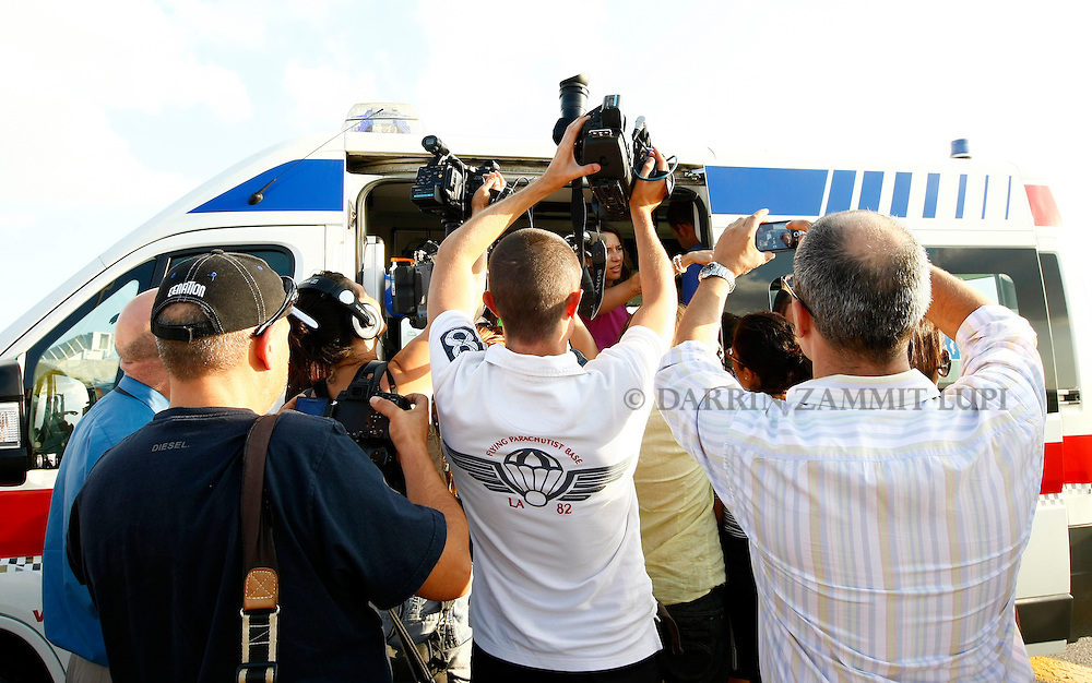 Members of the media crowd around an ambulance door trying to get pictures of Shwejga Mullah of Ethiopia after she arrived at Malta International Airport,outside Valletta September 15, 2011. An Ethiopian nanny in the Gaddafi household who suffered horrific burns after she did not stop one of Muammar Gaddafi's grandchildren crying, has arrived in Malta for specialised medical treatment. Shwejga Mullah was recently discovered weak and alone in the home abandoned by Muammar Gaddafi's son Hannibal. She said that  Hannibal Gaddafi's wife Aline threw boiling water over her when she did not stop Hannibal Gaddafi's daughter crying and refused to beat the child. The nanny was brought over in a private plane chartered by the Maltese government.    REUTERS/Darrin Zammit Lupi (MALTA)