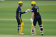 Brad Taylor(left) and Jimmy Adams of Hampshire punch gloves as Jimmy Adams finds the boundary  during the Royal London One Day Cup match between Hampshire County Cricket Club and Essex County Cricket Club at the Ageas Bowl, Southampton, United Kingdom on 23 May 2018. Picture by Dave Vokes.