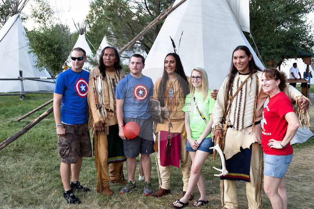A family poses with a group of Native Americans dressed in traditional costumes at the Indian Village during Cheyenne Frontier Days July 25, 2015 in Cheyenne, Wyoming. Frontier Days celebrates the cowboy traditions of the west with a rodeo, parade and fair.