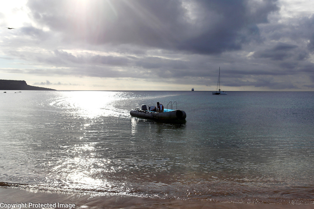 A zodiac driver steers a zodiac to shore off of Florian Island in the Galapagos.