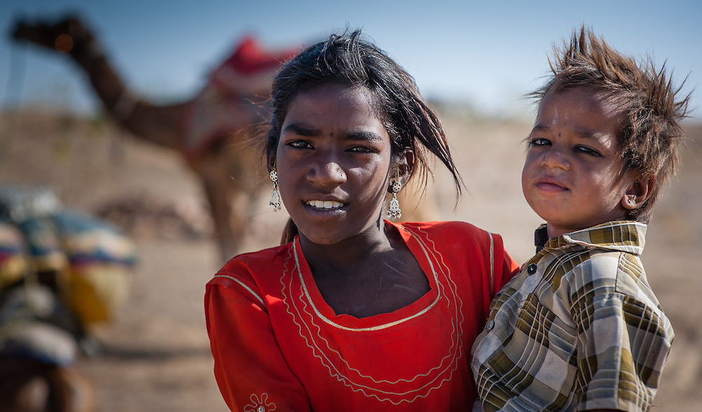 Girl carrying little brother in desert (India)