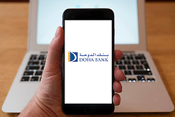 Using iPhone smart phone to display website logo of Doha Bank in Qatar