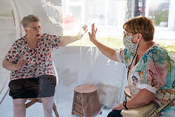 A woman touches her mother's hand through a plastic curtain as she visits her in a bubble at Fondation Shadet Vercoustre nursing home on May 27, 2020 in Bourbourg near Gravelines, France, where a double entry bubble has been installed to allow visits without risk of contamination, as part of a prophylactic measure against the spread of the Covid-19 disease caused by the novel coronavirus. Relatives and residents each enter the tent through a different entrance to find themselves in the same room, separated by a transparent plastic canvas. These bubbles were originally designed for tourism by the company. Photo by Julie Sebadelha/ABACAPRESS.COM