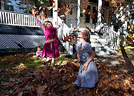 Sharita 3, and Diane 6, Longenecker play in fleshly raked leaves while their baby sister Rosalie looks on.
