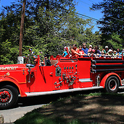 Adults and children enjoy a vintage fire engine ride during the May Fair at Saint Mark's Church, New Canaan, Connecticut, USA. 12th May 2012. Photo Tim Clayton