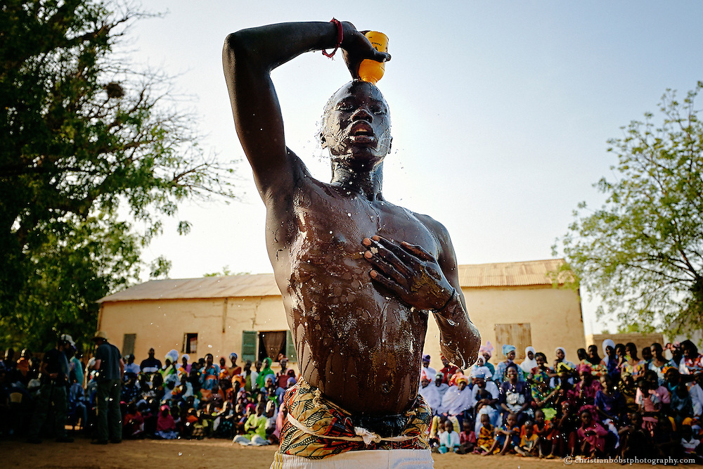 April 20, 2012. A young wrestler pours a magic potion over him at a small competition in the Soune, a small village near Thiès. In almost every village in Senegal there are occasional organised wrestling matches.