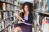Female university student studying in library, portrait