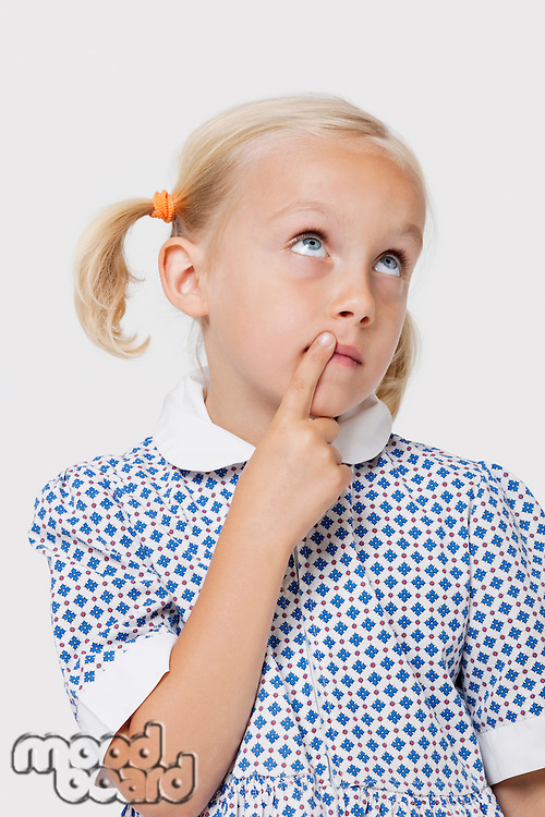 Young Caucasian girl thinking with finger on lips over white background