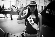 "A woman dressed in military garb and a sash that reads ""Kamikaze"" salutes next to a war-time military aircraft at a museum in the grounds of Yasukuni Shrine in Tokyo, Japan..Every year on August 15, the day Japan officially surrendered in WWII, tens of thousands of Japanese visit the controversial shrine to pay their respects to the 2.46 million war dead enshrined there, the majority of which are soldiers and others killed in WWII and including 14 Class A convicted war criminals, such as Japan's war-time prime minister Hideki Tojo. Each year speculation escalates as to whether the country's political leaders will visit the shrine, the last to do so being Junichiro Koizumi in 2005. Nationalism in Japan is reportedly on the rise, while sentiment against the nation by countries that suffered from Japan's wartime brutality, such as China, has been further aggravated by Japan's insistence on glossing over its wartime atrocities in school text books..Photographer:Robert Gilhooly.Photographer:Robert Gilhooly"