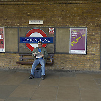 Man reading a newspaper on the platform at Leytonstone underground station on the Central line