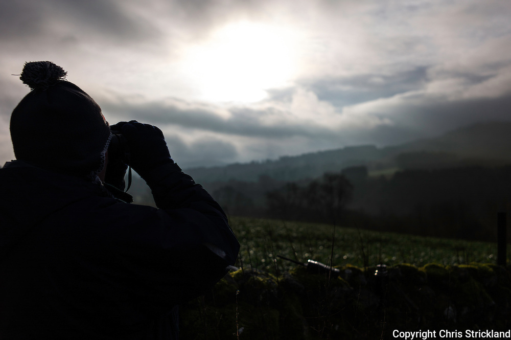 A foot follower looks out across Jed country through binoculars as he studies hounds from a distance.