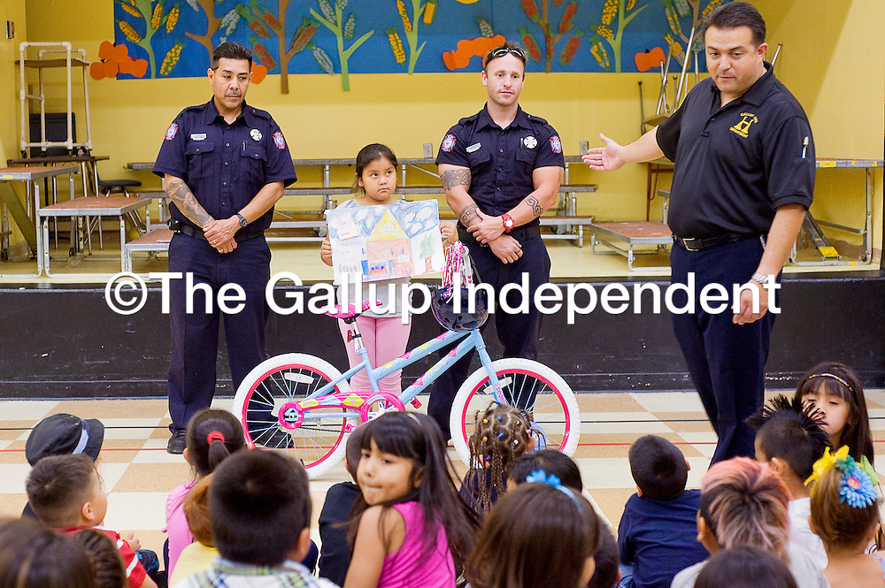 110212       Cable Hoover<br /> <br /> Lincoln Elementary first-grader Jayna Becenti, center, holds her winning drawing and stands with Gallup firefighters Artie Sandoval, left, and Adam Halvorsen while Chuy Morales, right, presents her with a bicycle Friday at Lincoln Elementary School in Gallup.