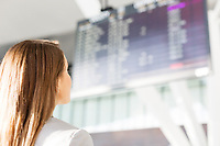 Businesswoman looking at flights display screen in airport