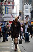 A woman listens to music on headphones as she walks down a Hong Kong street.