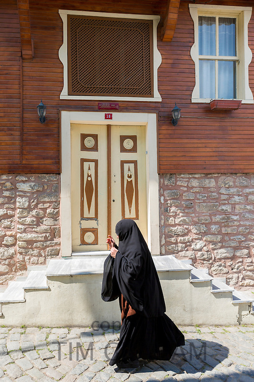 Muslim woman in traditional niqab veil clothing in the area of Kariye Muzesi, Edirnekapi in Istanbul, Republic of Turkey