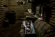 SAN CASIMIRO, VENEZUELA - AUGUST 21, 2017: The emaciated body of 17-month old, Kenyerber Aquino Merchán was prepared for burial in his family's kitchen. Kenyerber starved to death -  weighing only 8.8 lbs - the weight of a newborn baby. He was born healthy, but his mother, María Carolina Merchán, 30, became infected by the Zika virus when Kenyerber was just three months old. She had to be hospitalized when she fell ill to the Zika related Guillain-Barré Syndrome - that caused her to lose muscle function in her arms and legs, and made it impossible for her to continue to breast feed Kenyerber. The economic crisis in Venezuela has led to widespread shortages of infant formula, and when the family could not access it to feed Kenyerber, they had to improvise - feeding him what they could find: cream of rice or cornstarch mixed with whole milk, neither of which could provide him the nutrients he needed. He was first admitted into the hospital for malnutrition when he was 9 months old - and was in and out of the hospital for treatment for malnutrition until he died on August 19, 2017 at a public hospital outside of Caracas. The family struggles to afford enough to eat on father Carlos Aquino's wages as a construction worker, and they had to borrow money and make sacrifices to be able to bury Kenyerber. The family held his wake a family home, to cut costs - and hired a young mortician to come to the house and prepare Kenyerber's body for burial. The mortician wiped away blood, and injected the body with embalming chemicals on this well-worn couch in the kitchen - next to a refrigerator with no food inside it. Then he dressed the body and sealed it inside a small gray coffin.