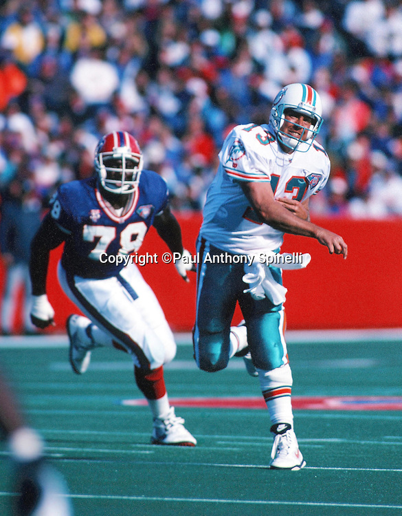 Miami Dolphins quarterback Dan Marino (13) throws a pass while chased from behind by Buffalo Bills defensive end Bruce Smith (78) during the NFL football game against the Buffalo Bills on Oct. 9, 1994 in Orchard Park, N.Y. The Bills won the game 21-11. (©Paul Anthony Spinelli)