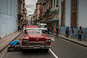 A mechanic tries to fix a broken down car in a busy street in Havana, Cuba.