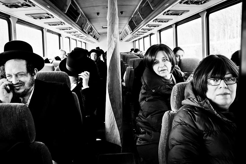 L'autobus che va da Williamsburg a New Square, Upstate e` un autobus della linea Monsey Trail ed e` severamente vietato per gli autisti e/o gli impiegati della linea di bus utilizzare la &quot;mechiza&quot;, il divisorio tra uomini e donne che si vede nella foto per motivi di discriminazione razziale. <br /> Nei gruppi di ebrei ultra-ortodossi come sono quelli di Monsey o New Square, la divisione tra uomini e donne e` obbligatoria. Il divisiorio, nascosto di solito in uno degli sportelli del bus, e` quindi affisso all`inizio di ogni viaggio dal primo uomo ebreo ortodosso a salire sull`autobus. <br /> Verra` poi tolto dall`autista alla fine della corsa per poi essere riposizionato di nuovo dal prossimo passeggero. Lo stato di New York proibisce severamente quest'usanza per via del messaggio di segregazione razziale tra uomini e donne implicato da tale usanza. Quindi il rituale e` a rischio e pericolo dei passeggeri che pero` non sembrano avere alcun problema in merito. Foto scattata il 9 Marzo, 2014.