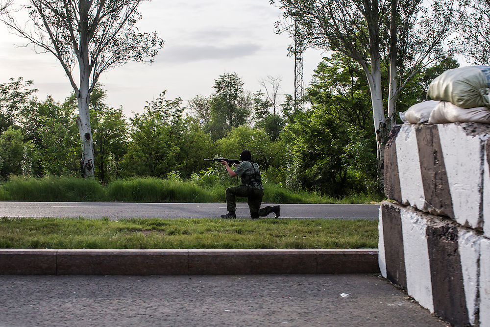 DONETSK, UKRAINE - MAY 22:  A Ukrainian soldier trains his gun on a vehicle at a checkpoint on May 22, 2014 in Donetsk, Ukraine. An attack at a military checkpoint earlier in the day in nearby Volnovakha killed a reported fifteen soldiers injured 31. (Photo by Brendan Hoffman/Getty Images) *** Local Caption ***