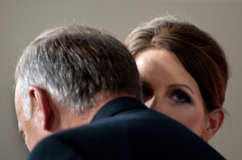 Rep. MICHELE BACHMANN (R-MN) whispers to Rep. STEVE KING (R-IA) during a news conference on Capitol Hill Wednesday about the debt ceiling and military benefits.