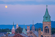 The iconic church steeples line the skyline leading to the capitol building of Charleston, West Virginia as the full moon hangs in the late evening pastel sky.