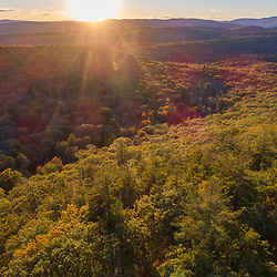 Drone view of sunset and the forest on Mount Eleanor and Rattlesnake Mountain in New Durham, New Hampshire.