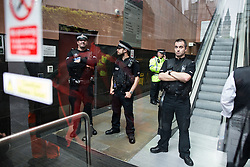 © Licensed to London News Pictures . 02/09/2015 . Manchester , UK . NB: IMAGE IS SHOT ON TO COURT PRECINCT . Police block the doorway as , outside , protesters stand holding antifascist flags and complaining about a trial involving an anti-fracking protester , at Manchester Magistrates' Court , after protesters stormed the court . Photo credit : Joel Goodman/LNP
