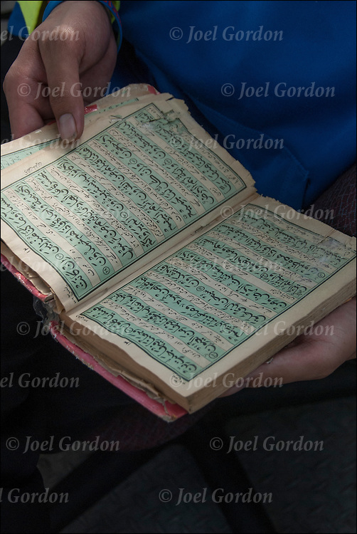 Close up of young Muslim male daily reading the Quran at work when it is not busy.<br /> <br /> Quran or Qur'an, is the central religious text of Islam, which Muslims believe to be the verbatim word of God ( Allah) and is regarded widely as the finest piece of literature in the Arabic language.