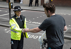 © Licensed to London News Pictures. 04/06/2017. London, UK. A passing cyclist gives a bottle of water to a police woman on duty near Borough Market after an attack by three men killed seven and injured at least 48. Police shot three attackers dead after they deliberately drove their van at people on London Bridge and then stabbed drinkers at bars in nearby Borough Market. Photo credit: Peter Macdiarmid/LNP