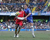 Photo: Lee Earle.<br /> Chelsea v Portsmouth. The Barclays Premiership. 25/02/2006. Chelsea's John Terry (R) goes in high on Benjani Mwaruwari.