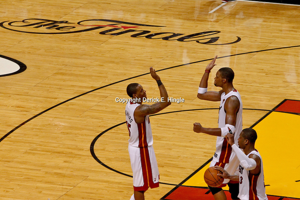 Jun 19, 2012; Miami, FL, USA; Miami Heat point guard Mario Chalmers (15), power forward Chris Bosh (1) and shooting guard Dwyane Wade (3) celebrate following a win in game four in the 2012 NBA Finals against the Oklahoma City Thunder at the American Airlines Arena. Miami won 104-98. Mandatory Credit: Derick E. Hingle-US PRESSWIRE