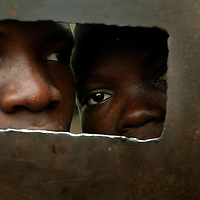 Two boys look through hole in prison door, Cotonou, Benin september 2003 - The prison of Cotonou has a part reserved for the young criminals. Many of these young criminals are street children who consume drugs.  They have been put in prison for the use, possession and/or trade of drug; and also often for violence and rape. Visiting room.