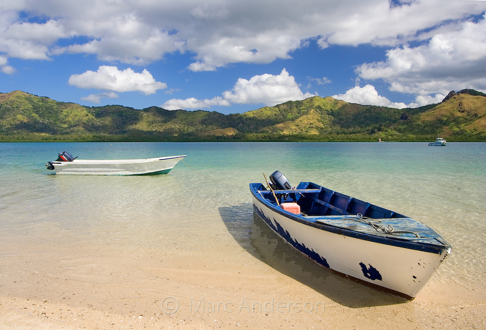 Small boats on a beautiful beach on a tropical island in Fiji..
