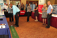 Bettina Buscemi of Day Air Credit Union and (from right) Sam Slater of Cooperative Business Services, LLC and Mary Cook of Universal 1 Credit Union watch as Alfonzo Woodie of Miami Valley Career Services tries to win chocolate from the DACC during a Dayton Area Chamber of Commerce Business After Hours at the NCR Country Club in Kettering, Wednesday, July 25, 2012.  The Chamber was promoting the 2012 Chamber Challenge, their 20th annual golf tournament and silent auction held at the NCR Country Club in September.