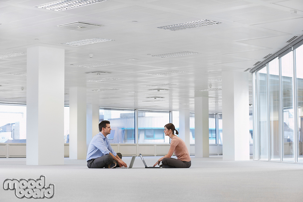 Two office workers sitting face to face using laptops on floor of empty office space