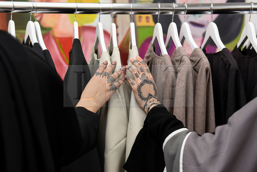 © Licensed to London News Pictures. 18/02/2017. London, UK.   Women with henna on their hands browse garments at the UK's first London Modest Fashion Week taking place this weekend at the Saatchi Gallery.  The two day event sees 40 brands from across the world come together to showcase their collections for Muslim and other religious women. Photo credit : Stephen Chung/LNP