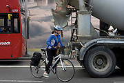 Woman cyclist starts to overtake a stationary cement mixer lorry in Shoreditch, London.