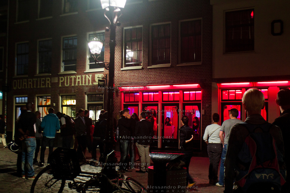 a group of tourists watching the red light district windows in Amsterdam.