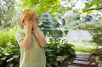 Girl (3-4) standing in garden covering eyes